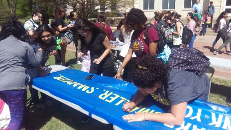 Chanel Hurd and other students sign a banner thanking alumni for donating at the TAG Day event. The banner will be displayed at future alumni events. Photo by Hannah Onder