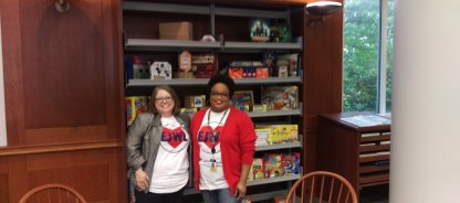 West Library director Elizabeth Howard and reference and instruction librarian Cassandra Ifie pose in front of the new game and amv shelf a stop on the National Library Week scavenger hunt. Photo by Hannah Onder