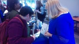 Senior psychology major Paola Estrada talks with a Jostens representative about dog tags. Photo by Hannah Onder