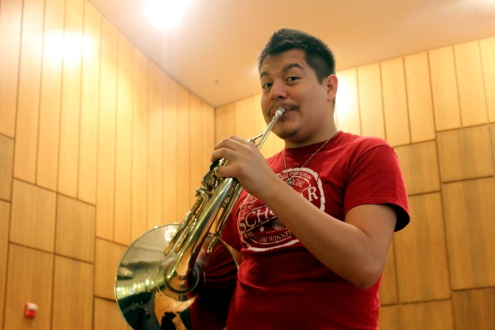 Senior music major Luis Calderon poses with his French horn in Nicholas Martin Hall. Calderon found his passion for music in his high school band. Photos by Hannah Onder