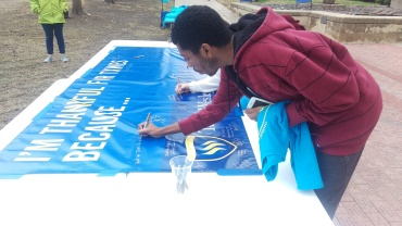Senior psychology major Tyler Jackson signs the banner thanking alumni for their donations. Photo by Hannah Onder