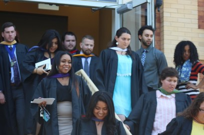 Graduating seniors walk outside of Nicholas Martin Hall after the robing ceremony. Photo by Hannah Onder