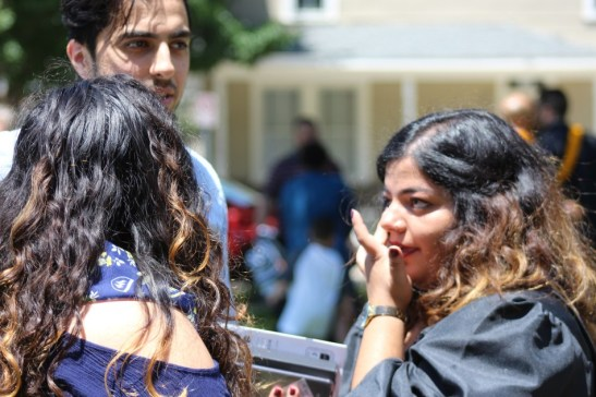 Senior political science major Andrea Upadhyay talks with friends after the robing ceremony. Photo by Hannah Onder