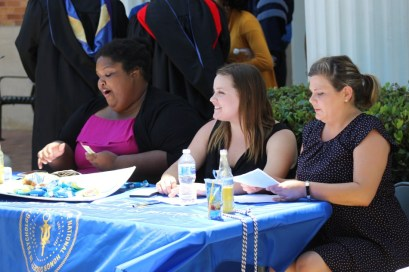 Psi Chi officers work to pre-sell DVDs of graduation outside of Nicholas Martin Hall. Photo by Hannah Onder