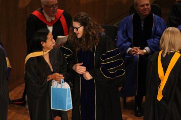 Senior sociology major Laura Velazquez (left) is robed by Dr. Alison Simons. Photo by Hannah Onder