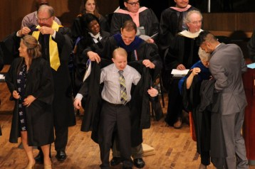 Senior history major Clark Williams is robed by Dr. Christopher Ohan. Photo by Hannah Onder