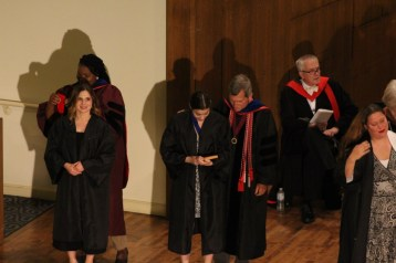 Senior English major Ann Levy (looking down) receives a gift while being robed. Photo by Hannah Onder