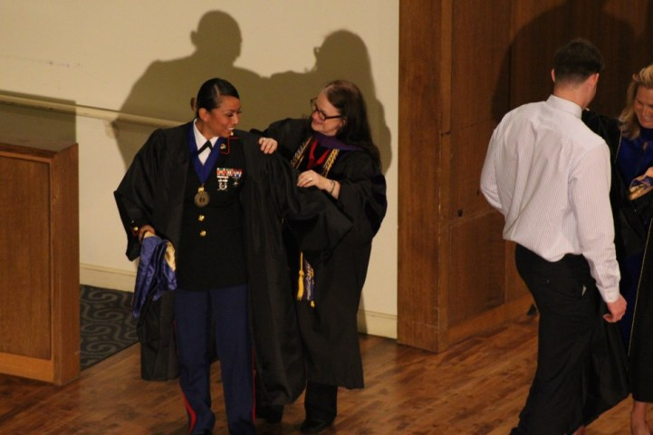 Dr. Michelle Payne robes senior political science major Tristeza Ordex-Ramirez. Photo by Hannah Onder