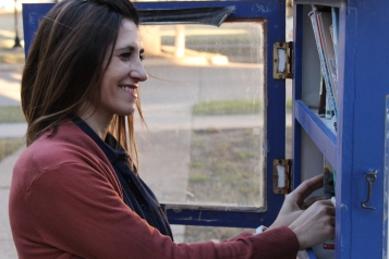 Robin Rivera, a Master of education student, who has a focus in reading, looks through books left in the mini library in front of Dan Waggoner. Photo by Hannah Onder